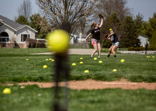 Granville seniors Kara Gunter and Aubrionna Claypool work on fielding balls at Gunter's home. With the closures of schools in March all spring sports have also been put on hold, but many players continue to practice their skills in the hopes they will still be able to play with their teams.
