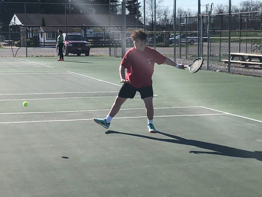 Watkins Memorial junior Chris Burns hits with teammates Wednesday on the school's tennis courts. The spring sports seasons remained postponed at least through April.