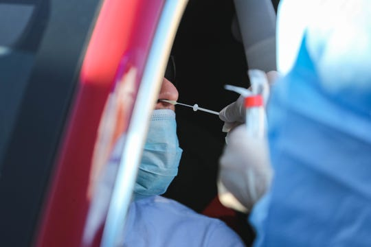 Medical staff test patients at a drive-thru coronavirus testing, set up in Sunland Park at the Sunland Park Public Health Office on Wednesday, April 8, 2020.