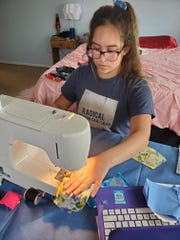 Mickeyla Van Patten, 14, sews protective face masks intending to stop the spread of coronavirus, April 6, 2020 at her home in Carlsbad.