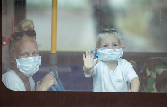 Devin Turner, left, and her son Dakota Brown, 2, sit inside a parked bus as the rain comes down in Palm Springs, Calif., on April 7, 2020. SunLine Transit requires passengers to cover their mouth and nose to stop the spread of coronavirus.
