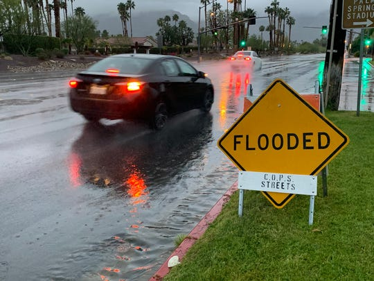 A sign advises drivers of a flooded stretch of Ramon Road in Palm Springs Wednesday, April 8, 2020. A storm is expected to drop an inch of rain on the city by the end of the week.