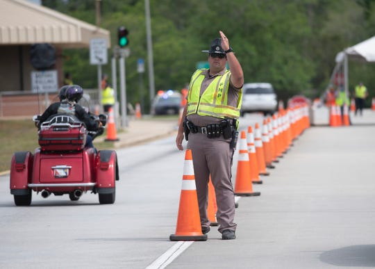 The Florida Highway Patrol monitors the flow of traffic entering a COVID-19 checkpoint at the Florida/Alabama State line on Interstate 10 on Tuesday, April 7, 2020.