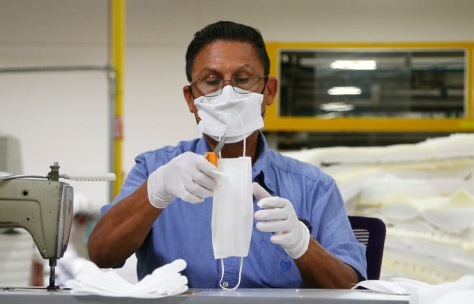 Jose Gonzalez works on making face masks as the Ortho Mattress company which is repurposing their factory to make the masks due to the coronavirus pandemic Monday, April 6, 2020, in Phoenix. Ortho Mattress has a daily goal of making 1,000 of the masks supporting the demand in the community.