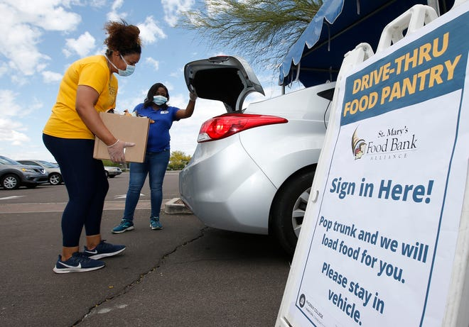 Volunteers from Phoenix College hand out St. Mary's Food Bank donated food boxes in a drive thru set up for the general public at the Phoenix College campus due to the coronavirus Wednesday, April 8, 2020, in Phoenix.