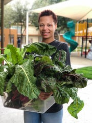 Yahnae Ferguson poses with rainbow greens she harvested from the UMOM garden. Ferguson has been living in the UMOM emergency family shelter since Feb. 2020.