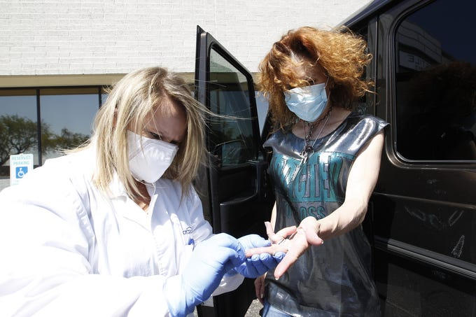 An ARCpoint Labs worker pricks a customer's finger for COVID-19 testing that can tell whether or not the customer has antibodies against the new coronavirus.