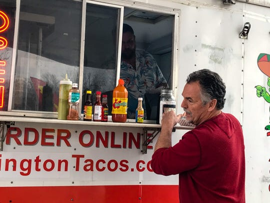 Chris Mader orders Mexican food from El Hombre Grande food truck owner Bretton Jones at Huron Food Fleet's new Port Huron location on April 7, 2020.