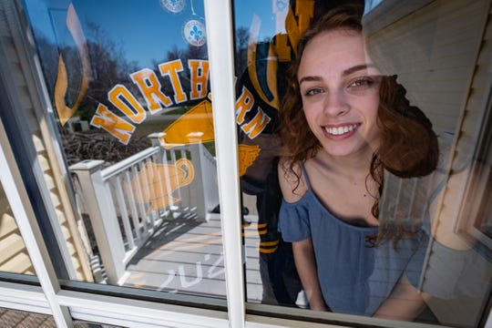 Port Huron Northern senior Paige Cronce looks out of the windows on the front door of her family's Port Huron home Wednesday, April 8, 2020. Because of the coronavirus pandemic, Cronce wasn't able to finish her senior year of high school, but to celebrate her accomplishments, her mother decorated the front door of their home.