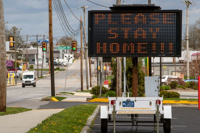 A Northern York County Regional Police traffic safety sign tells people to 'PLEASE STAY HOME !!!' in Manchester on Wednesday April 8, 2020.