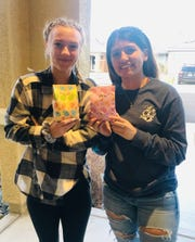 Bishop Manogue senior softball players Grace Miller (left) and Karla Rangel hold Easter bags from Manogue assistant coach Victoria Fox.
