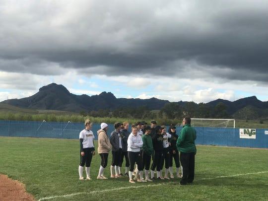 The Manogue softball players listen to coach Michael Bastian last month
