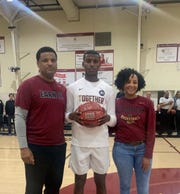Jaden Bradley is flanked by his parents Nate Sr. and Mialisha after scoring his 1,000th varsity point. Bradley was named the Gatorade player of the year in North Carolina and is a top recruit in the class of 2022.