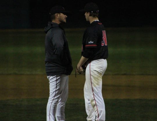 Simpson baseball coach Dan Tating visits freshman right handed pitcher Jake Alexander during a game against Holy Names University at Tiger Field in Redding on Feb. 1, 2020.