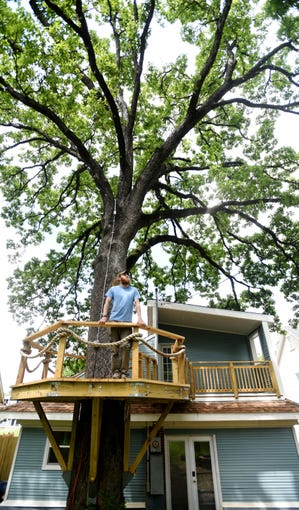 Jake Snyder from Catahoula Homes stands on the wooded fort that surrounds the Oak tree at the College Street house they recently completed in Highland.