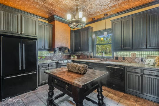 The stone backsplash in the kitchen matches the columns found throughout the property.