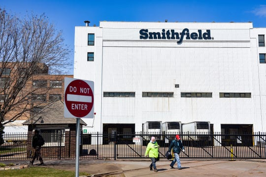 Smithfield Foods, Inc. employees wear masks as they leave at the end of their shift on Wednesday, April 8, at the food processing plant in Sioux Falls.