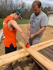 Caeden and Deke Aleshire work on building a cross for their family Easter service this year. Normally the Crimora family would celebrate Easter at their church in Waynesboro, but they'll be holding a small family service at home this year.