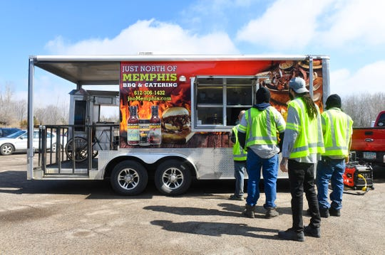 Employees line up for lunch from the Just North of Memphis food truck at Integrated Recycling Technologies Tuesday, April 7, 2020, in St. Cloud.