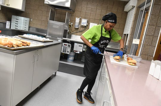 """Chevy's Pit LLC owner Shavawn """"Chevy"""" Crume prepares food Monday, April 6, 2020, at the kitchen space she rents from Atonement Lutheran Church in St. Cloud."""
