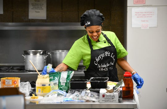 """Chevy's Pit LLC owner Shavawn """"Chevy"""" Crume smiles while preparing food Monday, April 6, 2020, at the kitchen space she rents from Atonement Lutheran Church in St. Cloud."""