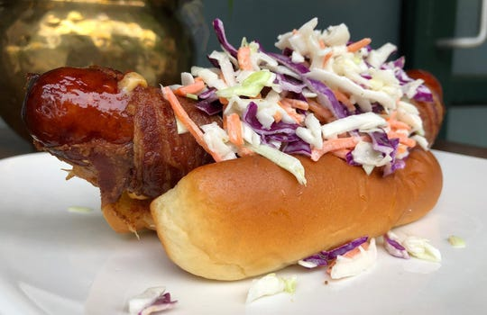 Sage's new Deliverance Dog creation features bacon-wrapped sausage with coleslaw, paired with rosemary French fries.
