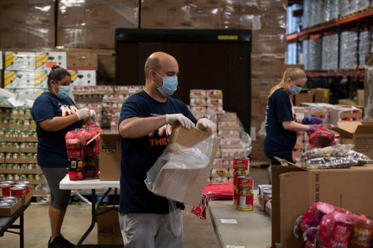 St. Lucie County Library employees (from left) Taryn Bagley, Gabe Gresham and Samantha Schimpf, with the help of other St. Lucie County staff, create hundreds of emergency food bags with chili, canned chicken, canned soup, tomato sauce, peanut butter and trail mix to be dispensed by the Treasure Coast Food Bank on Wednesday, April 8, 2020, at the food bank's distribution center in Fort Pierce.