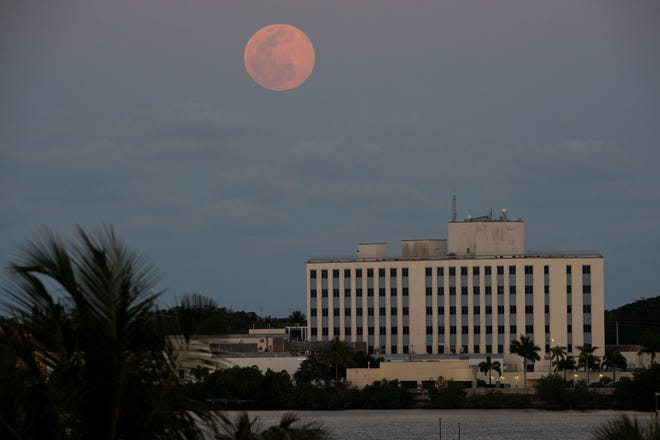As the sun set over the St. Lucie River, April's full moon, the brightest supermoon of the year, rose in the east over Cleveland Clinic Martin North Hospital on Tuesday, April 7, 2020, in Stuart, Fla. The hospital is a drive-thru testing site for COVID-19, the virus that caused a global pandemic that has forced millions of Americans to stay home. As of April 7, more than a dozen patients infected with coronavirus are being treated by Cleveland Clinic in Martin County.
