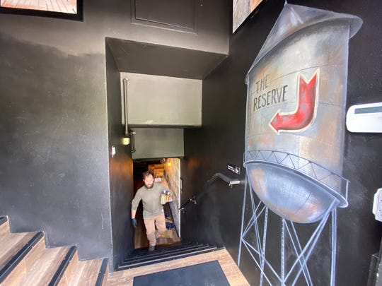 Paul Jones, beverage manager at Oak & Iron in Thousand Oaks, emerges from business' subterranean bar, The Reserve, with an order of craft cocktails and mixers to go.