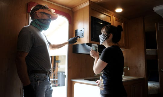 Mark Draganchuk, of Dragan RV, explains how his trailer works to Angie Mireles, a Ventura nurse. Healthcare workers are moving into RVs because they are worried they could have been exposed to COVID-19 and want to distance themselves from their families.