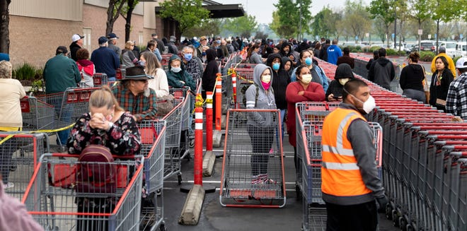 Shoppers, spaced by the width of a parking stall and a row of carts, wait to enter Visalia Costco on Wednesday, April 8, 2020.