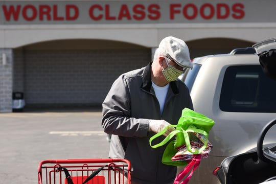 Waterville resident David O'Brien puts extra reusable bags into the trunk of his car while wearing a protective mask on Tuesday, April 7, 2020 at Chanatry's Supermarkets Inc. in New Hartford. [ALEX COOPER / OBSERVER-DISPATCH]