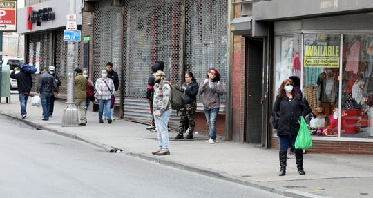 People waiting for the bus and pedestrians are pictured on Palisade Avenue in Yonkers on April 8, 2020.