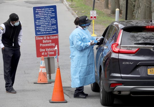 A security guard at the Hebrew Home at Riverdale takes the temperature of someone entering the facility April 8, 2020. Everyone entering the facility, including all staff, are checked for a fever before being allowed in the nursing home. Like other nursing homes throughout the nation during the coronavirus pandemic, the facility has stopped allowing residents to have visitors.