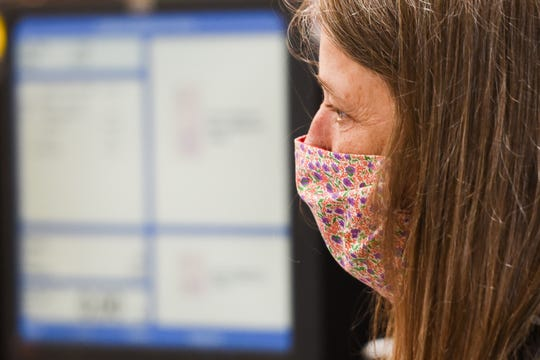 Chanatry's employee Kathy Keegan wears a protective mask while cashing customers out on Tuesday, April 7, 2020 at Chanatry's Supermarkets Inc. in New Hartford. Check-out registers also have a plastic barrier between workers and consumers for an added layer of protection.