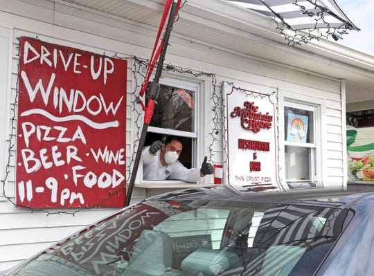 Danny DeMartino, the owner of Mountain House Pizza gives thumbs up at the newly built takeout window to accommodate customers during the coronavirus quarantine in Sparkill April 8, 2020.