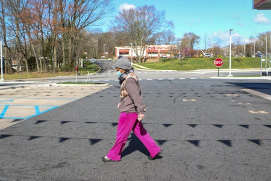 """Kena Ford walks towards the Circle K in Claymont on Wednesday, April 8. She's been wearing a mask in public from day one because she has asthma and is a breast cancer survivor. """"I've only been coming out once a week,"""" she said."""