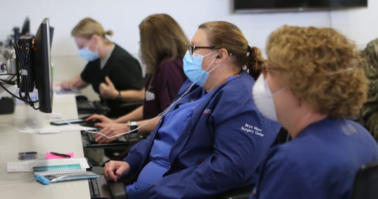 Nurses and national guard nurses conduct online training at the Adult Alternate Care Site at the Nemours/Alfred I. duPont Hospital for Children.