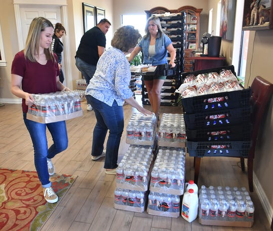 The Mindy Anderle Insurance agency, Sami Mathis, left, Yvette Reddell, Skylar Veitenheimer, Elaine Swift and Mindy Anderle, right, will offer a giveaway of bread, milk and bottled water for approximately 400 Friday morning.