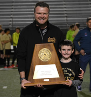 Rider soccer coach Dustin Holly and his son hold the 2000 state championship trophy