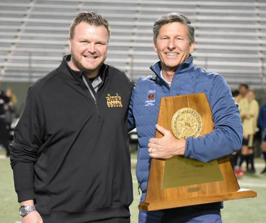Rider head coach Dustin Holly stands alongside former coach Kenny Catney in a ceremony that honored the 2000 state championship team on March 6 at Memorial Stadium