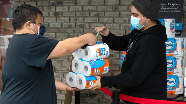 Lee Ho purchases toilet paper on Tuesday outside Masataco, a taco shop in Whittier, California.