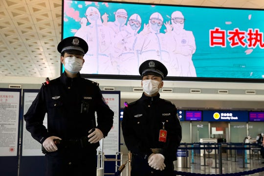 Police officers wearing face masks to protect against the spread of new coronavirus stand guard at Wuhan Tianhe International Airport in Wuhan in central China's Hubei Province, April 8, 2020.