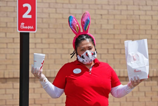 Amid COVID-19 concerns, fast food worker Silay Penalosa wears a mask and Easter bunny ears as she carries an order to customer a waiting outside a Chick-fil-A restaurant in Dallas, Tuesday, April 7, 2020.