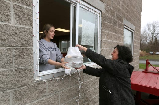 Apr 3, 2020; Webster, NY, USA; Abby Ferreri hands over an order to customer Paula Colombo at Rhinos Pizzeria and Deli in Webster, N.Y. on April 3, 2020. The restaurant converted a window in its dining room into a pickup window in response to the coronavirus outbreak.