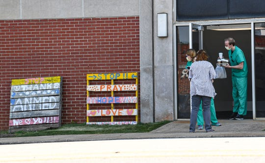 Employees look at two wood pallets left on a wall on South Fant Street at AnMed Health, painted with words of encouragement and thanks in Anderson Thursday.