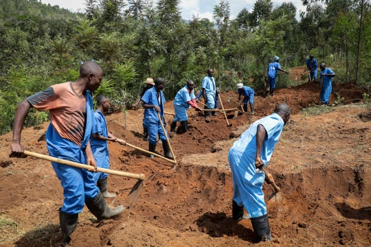Workers with Burundi's truth and reconciliation commission dig for human remains at the site of a mass grave at Bukirasazi hill, Karusi province, Burundi Monday, Feb. 17, 2020. Authorities in Burundi say they have opened six mass graves containing more than 6,000 bodies from unrest that occurred decades ago, the largest such discovery in years of work.