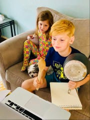 Grayson Beall, right, prepares his makeshift drum of a pot and wooden spoon for an online music class through Wylie Independent School District's at-home learning while sister, Maryn Beall and dog Zoe look on Thursday, April 9, 2020. Grayson is a student at Wylie East Elementary School.