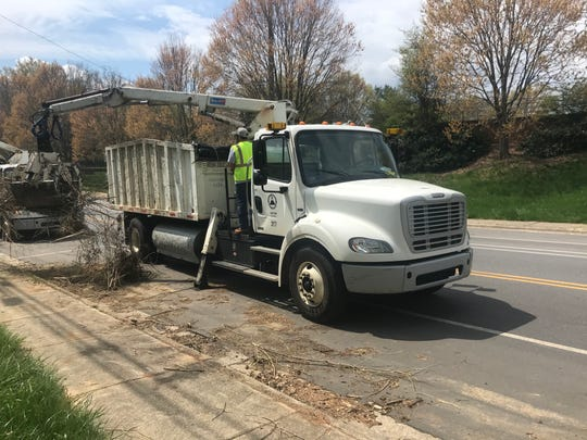 The city of Asheville continues to make brush pickups with a claw truck.