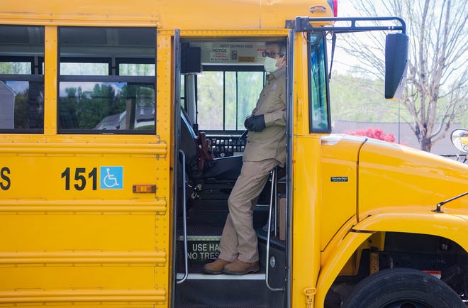 Dan Smith, an employee of the City of Asheville, stands on the steps of a meal school bus as he assists in delivering meals to children that attend Buncombe County Schools at the Hawthorne at Southside apartment complex on April 9, 2020.